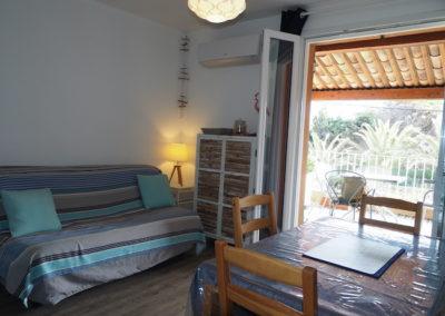 en intérieur, canapé, table et vaisselier avec vue sur terrasse ensoleillée