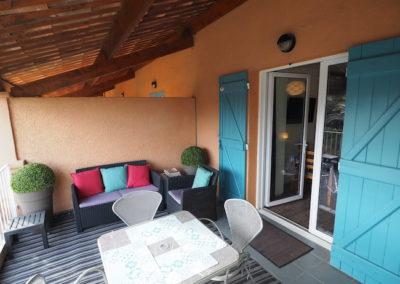 terrasse canapé coussins bleus rouges, table 4 chaises, porte fenêtre avec volets bleus sur studio ouverte
